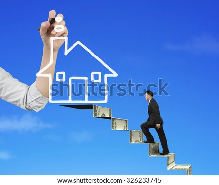 Businessman climbing the money stairs toward white house shape cloud with Female hand holding pen drawing, on blue sky background, side view. - stock photo