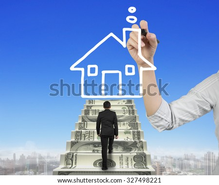 Businessman climbing the money stairs toward white house shape cloud with Female hand holding pen drawing, on sky cityscape background. - stock photo