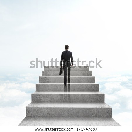 businessman climbing to stairs on sky background