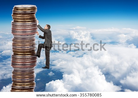 Businessman climbing up a huge stack of coins with sky background - stock photo