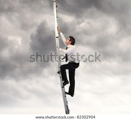 Businessman climbing up a ladder - stock photo