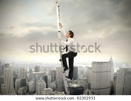 Businessman climbing up a ladder with cityscape in the background - stock photo