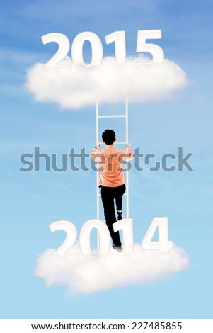 Businessman climbing upward on the cloud with number from 2014 to 2015 - stock photo