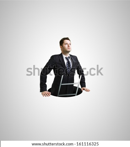 Businessman climbs out of the hole - stock photo