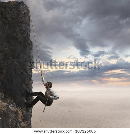 Businessman climbs the mountain. Concept of professional success - stock photo