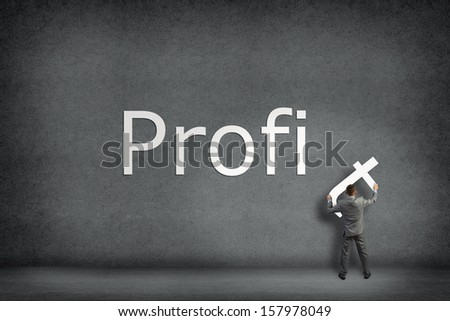 Businessman collects on the wall the word profit, holds the last letter - stock photo