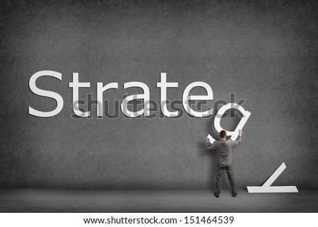 Businessman collects on the wall the word strategy, places the letter on the wall - stock photo