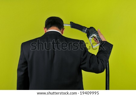Businessman committing suicide with a gas nozzle isolated on a green background