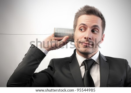 Businessman communicating through a can with a cable as it was a telephone - stock photo