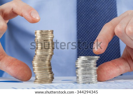 Businessman comparing stacks of coins, closeup shot