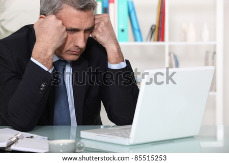 Businessman concentrating on his laptop - stock photo