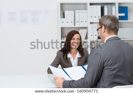 Businessman conducting an employment interview with an attractive young female applicant sitting opposite him at the desk in the office answering his question concerning her CV - stock photo