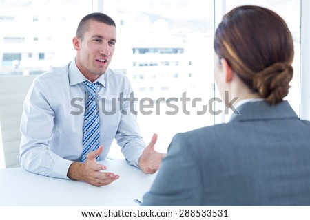 Businessman conducting an interview with businesswoman in an office - stock photo
