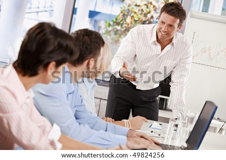 Businessman conducting business presentation in meeting room, talking smiling.
