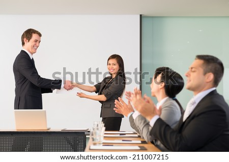Businessman congratulating Vietnamese manager, her colleagues applauding - stock photo