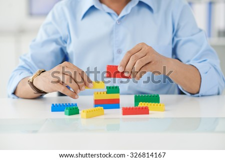 Businessman connecting lego details at his place of work
