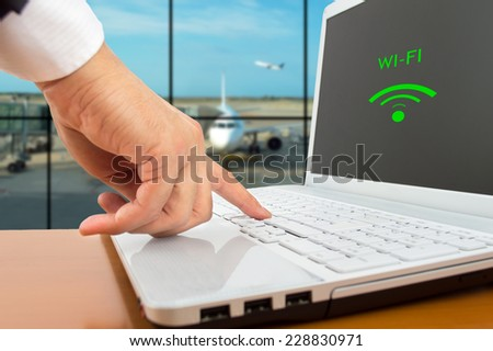 Businessman connecting to wi-fi at an airport - stock photo