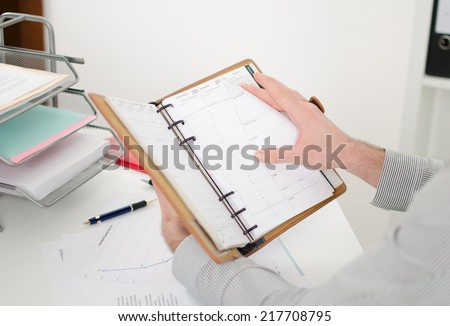 Businessman consulting his agenda at the office - stock photo