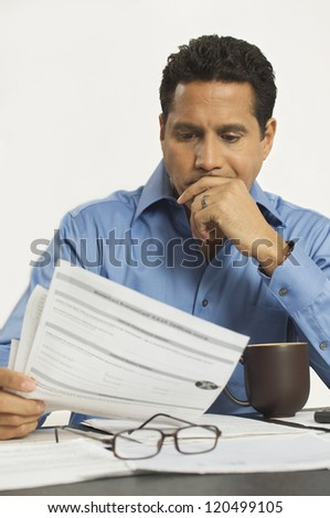 Businessman contemplating while reading a document at desk in office