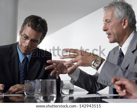 Businessman conversing while male colleague taking notes in conference room - stock photo