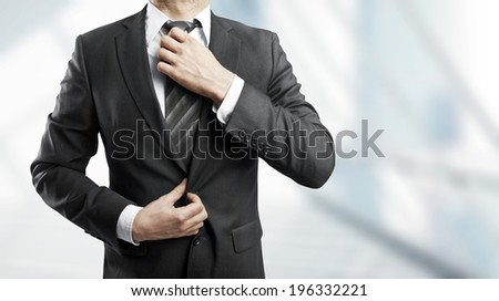 businessman corrects a tie on gray background - stock photo
