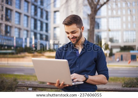 Businessman corresponding through internet by office building - stock photo