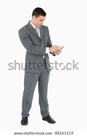 Businessman counting banknotes against a white background - stock photo