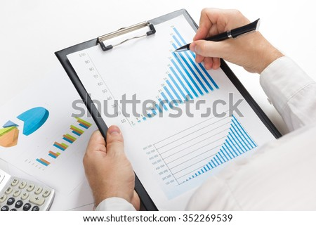 Businessman counting losses and profit working with statistics, analyzing financial the results. - stock photo