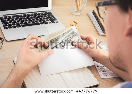 Businessman counting money above wooden office desktop with various items. Bribery and corruption concept