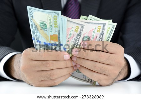 Businessman counting money,US dollar (USD) bills, on the table - soft focus - stock photo
