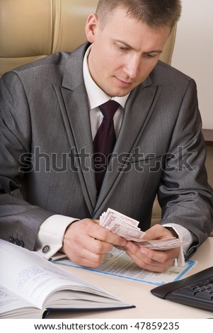 businessman counting ten euro banknotes sitting on the desk