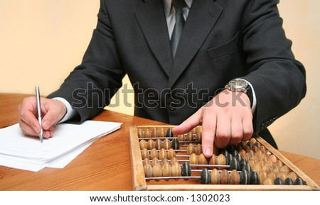 Businessman counting with an abacus - stock photo