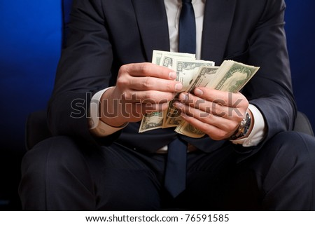 Businessman counts money in hands. - stock photo