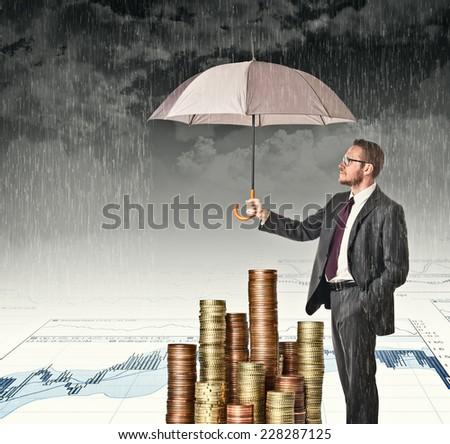 businessman cover his money with umbrella - stock photo