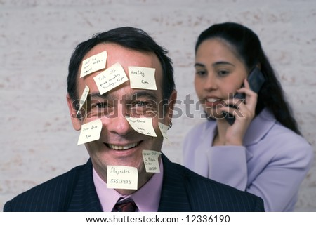 Businessman covered with sticky notes smiling at the camera while a female colleague chats on the phone behind him - stock photo