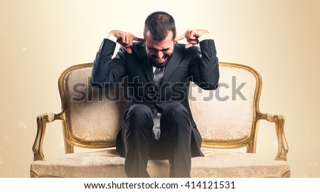 Businessman covering his ears