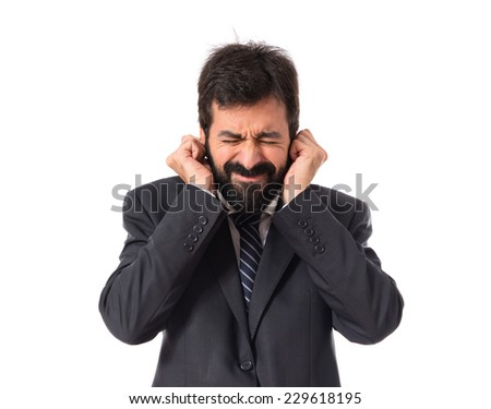 Businessman covering his ears over white background - stock photo