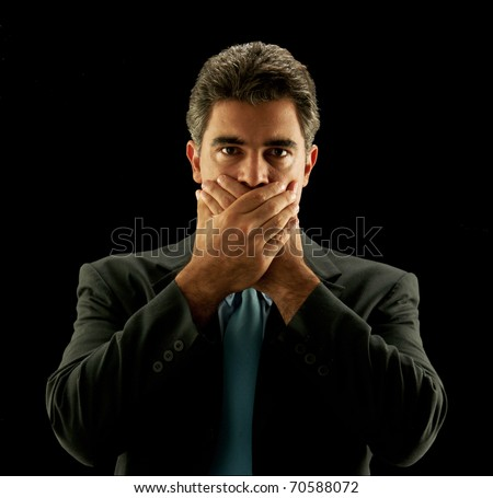 Businessman covering his mouth on black background. - stock photo