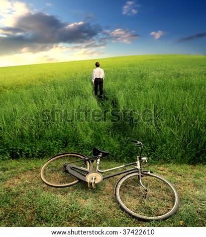 businessman crossing a grass field after a riding bike - stock photo