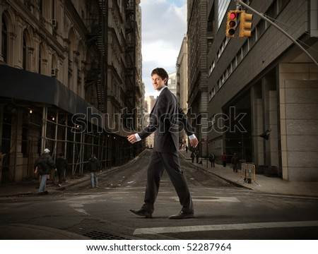 Businessman crossing a road - stock photo