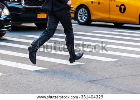businessman crossing a street in a hurry - stock photo