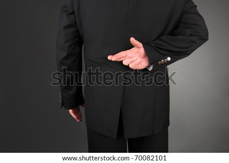Businessman crossing his fingers behind his back - stock photo