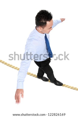 businessman crossing the small rope isolated on white background
