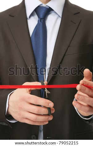 Businessman cutting a red ribbon with a pair of scissors, closeup - stock photo