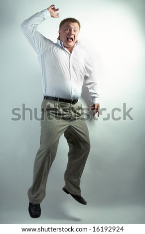 businessman dancing on the grey background - stock photo