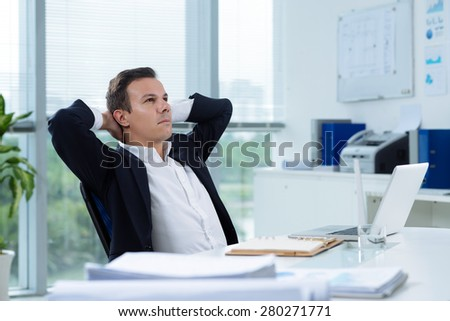 Businessman daydreaming in the office with hands behind his head - stock photo
