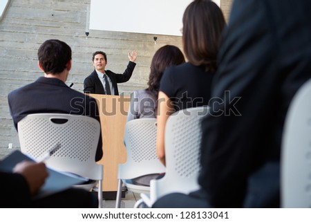 Businessman Delivering Presentation At Conference - stock photo
