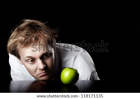 Businessman desaturated, lifeless and unmotivated looking at bright green apple for inspirational idea spark, abstract business concept - stock photo