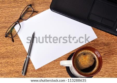 businessman desktop, coffee, laptop, glasses, a pen and  blank paper - stock photo