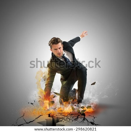 Businessman determined breaks the asphalt with force - stock photo